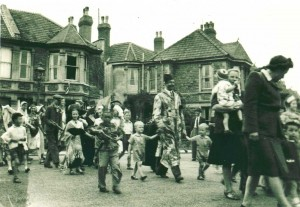 Victory fancy dress parade on the streets of Westbury Park, Bristol.  Billy dressed in a patchwork dressing gown and wearing a fez is leading his twin sons Christopher on his right, Paul on his left